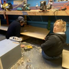 Brahm and Lee fit new shelves in bosun's stores